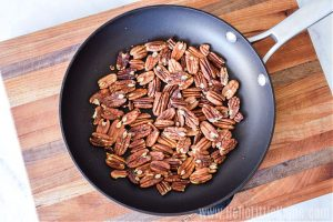 Toasted pecans in a skillet on a wood cutting board.