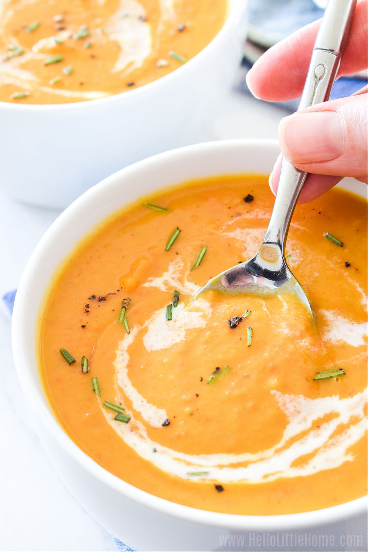 A hand holding a spoon in a bowl of the finished soup.