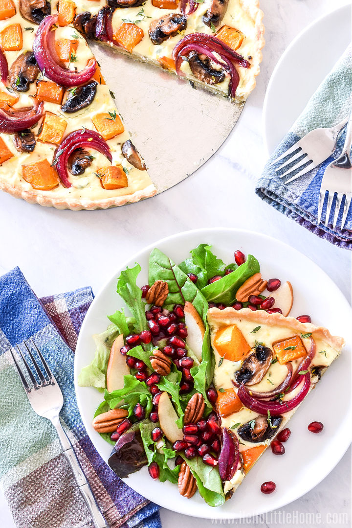 A marble counter topped with the finished tart and a sliced of it served on a place with salad.