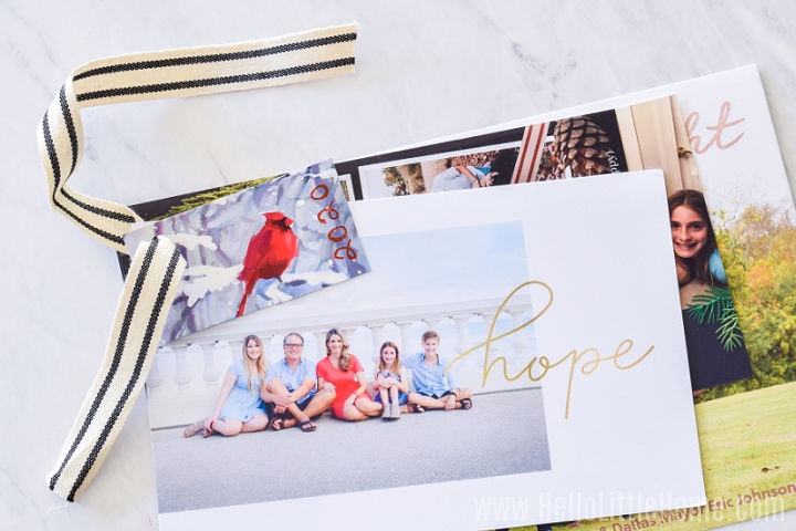 Photo cards on a marble counter with a piece of ribbon pulled through their holes.