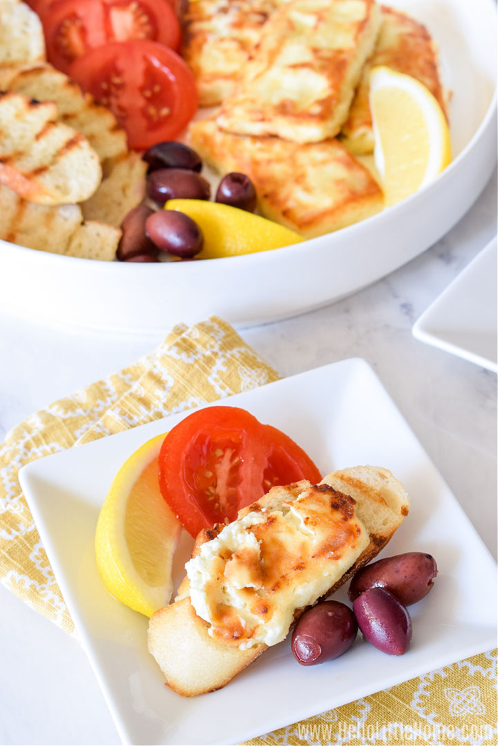 A square plate topped with feta, bread, and sides on a yellow napkin with a full platter in the background.