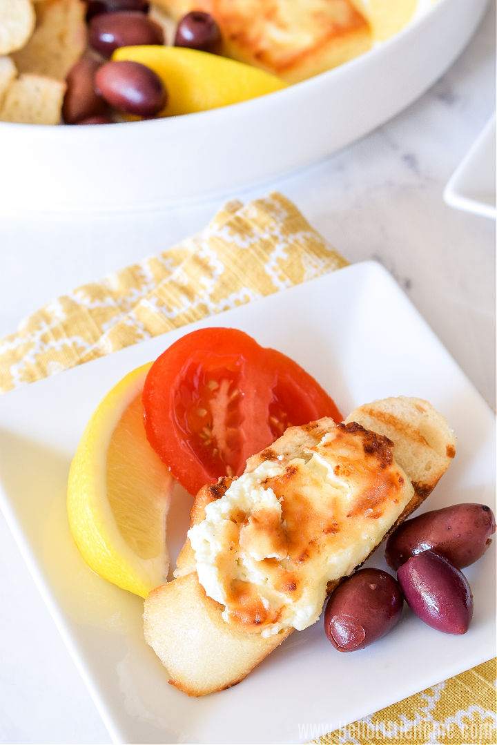 A square plate topped with feta spread on bread, olives, tomatoes, and a lemon wedge.