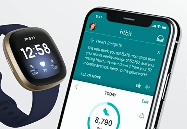 A fitness tracker next to a smart phone.
