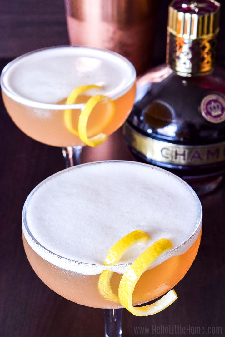 Two drinks garnished with a lemon twist on a wood table.