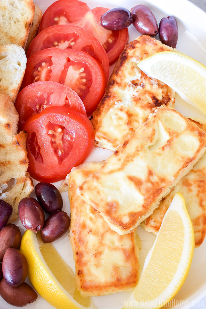 Closeup of the fried cheese, tomatoes slices, olives, lemon wedges, and bread slices on a platter.