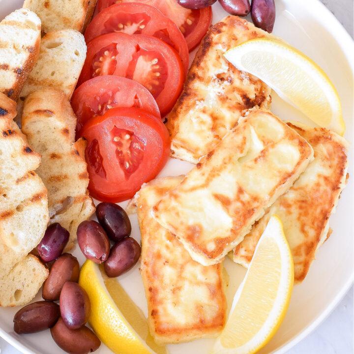 Feta Saganaki, tomatoes, bread, olives, and lemon wedges on a platter.