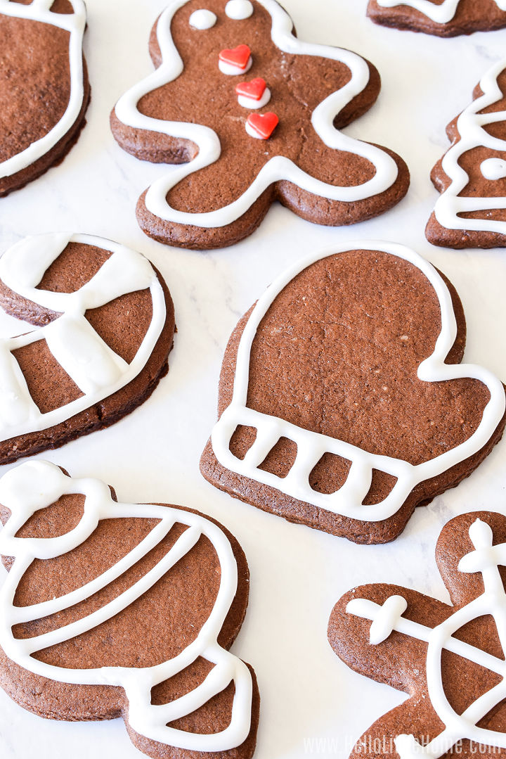 Cookies cut into different shapes and decorated with icing on a white counter.