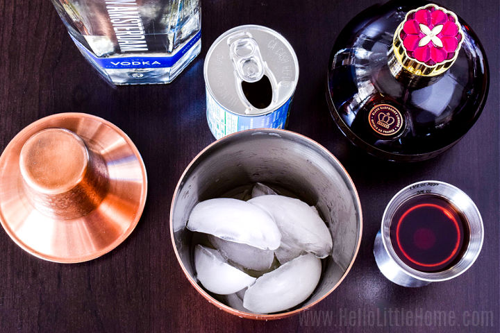 A cocktail shaker filled with ice and surrounded by the recipe ingredients.