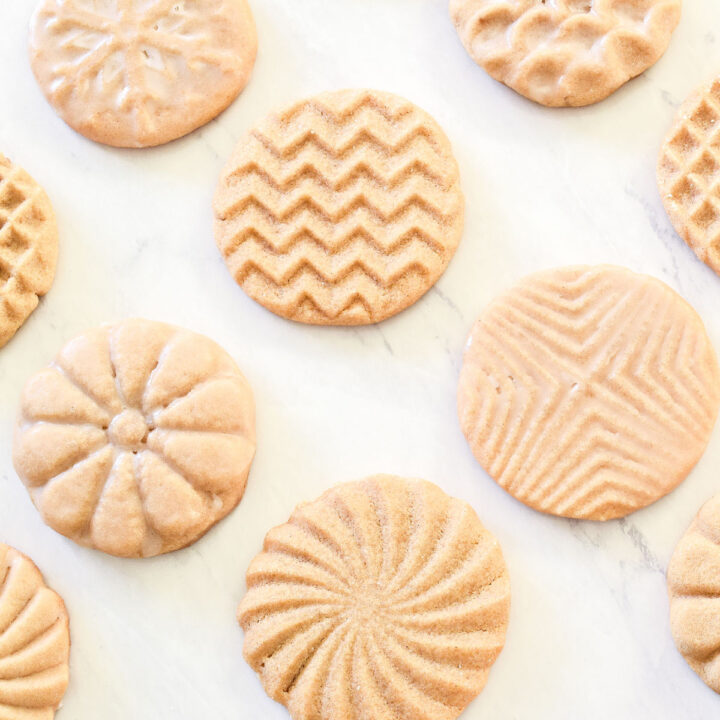 Stamped Cookies arranged on a marble counter.