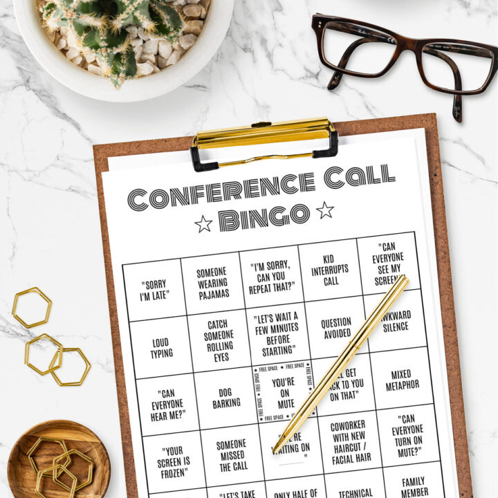 Printable Conference Call Bingo Card on a clipboard surrounded by paper clips, eye glasses, and a small plant.