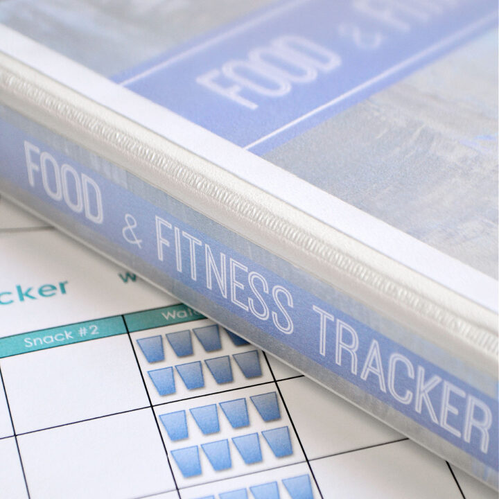 A sheet from the Free Printable Food and Fitness Tracker on a table with the journal in a binder on top of it.