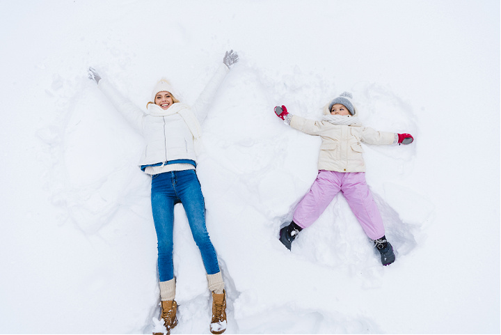 A woman and child making snow angels.