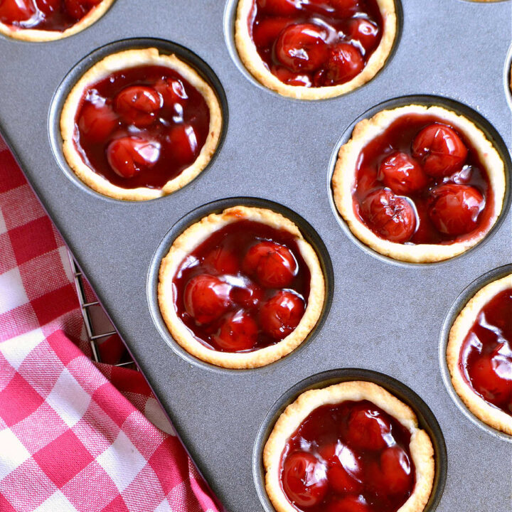 A muffin pan filled with Mini Cherry Tarts next to a checked napkin.