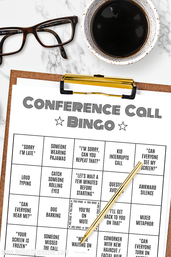 A office bingo card on a clipboard, eye glasses, and cup of coffee on a marble counter.