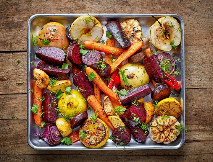 A baking sheet topped with roasted veggies.