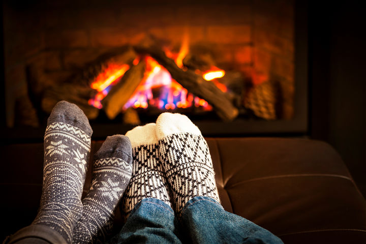 Two pairs of feet in front of a fireplace.