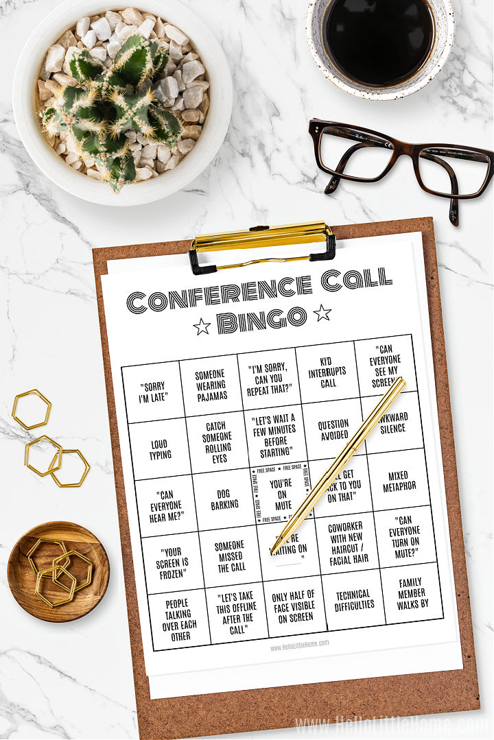 A video conference bingo card on a clipboard surrounded by a plant, eye glasses, and paper clips.