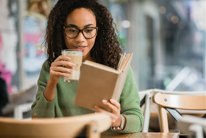 A woman reading a book in a cafe.