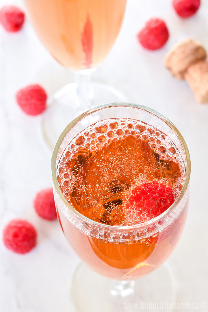An overhead photo of the finished drink surrounded by fresh raspberries on a marble counter.