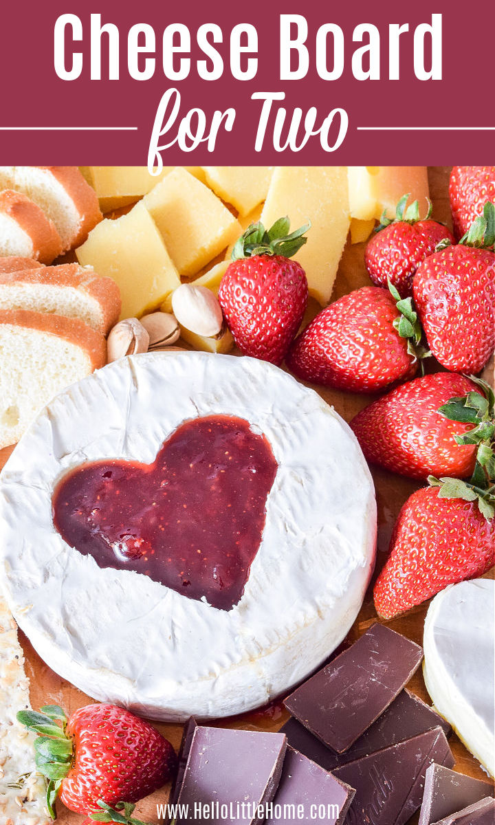 Brie with a heart cut out of its middle and other ingredients on a platter.