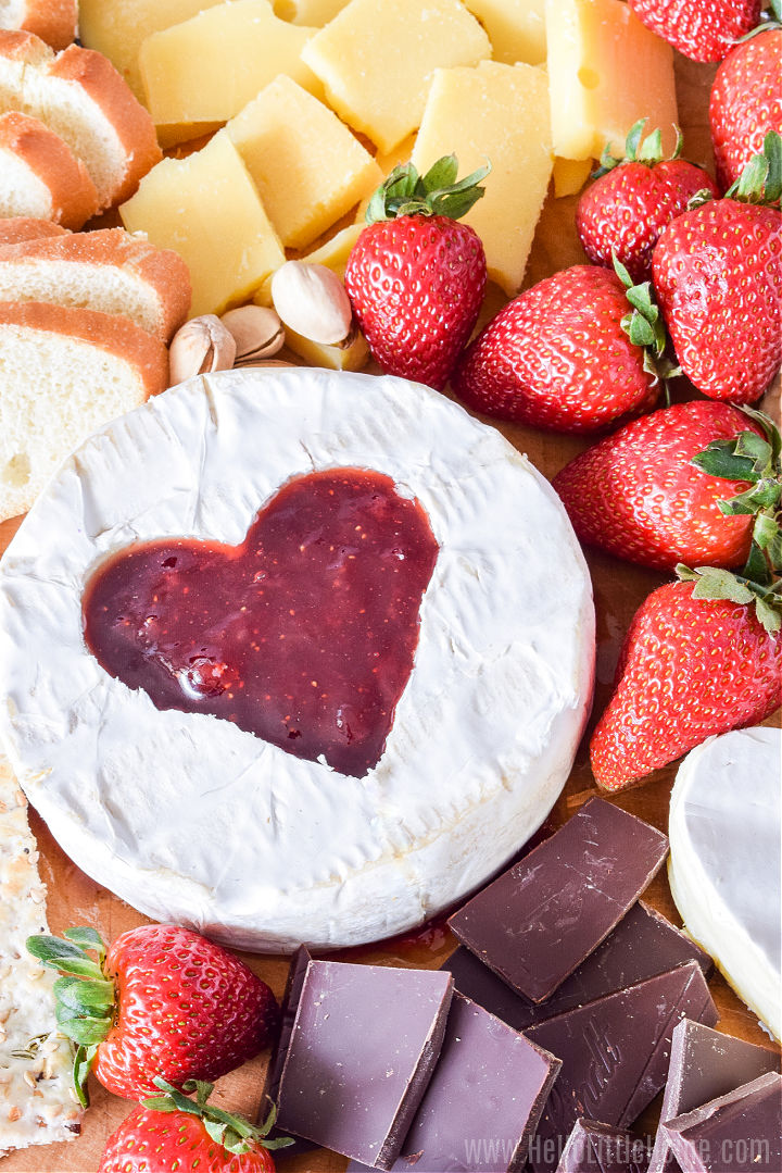 Closeup of round of brie with a heart cut out of the middle and filled with jam.