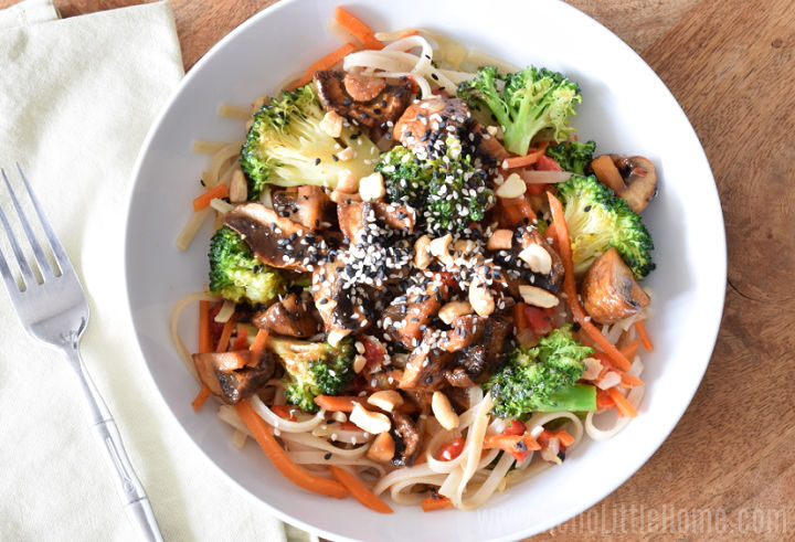 A white bowl filled with veggies and noodles.