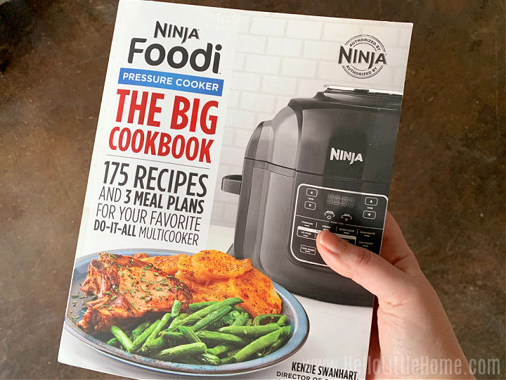 A woman's hand holding a cookbook.