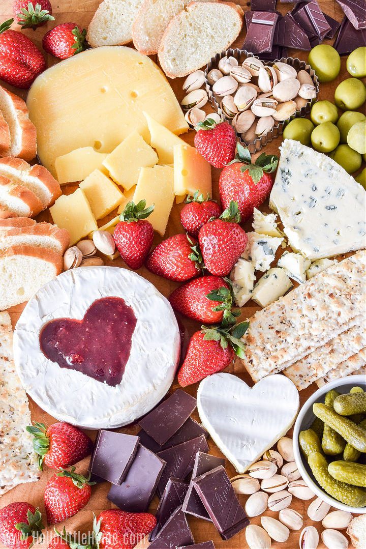 Cheese, nuts, fruit and more arranged on a wood board.