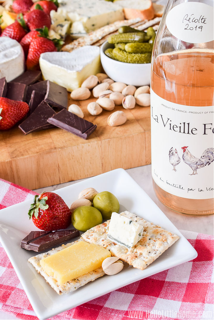 A small plate of food next to a bottle of wine with a cheese platter in the background.