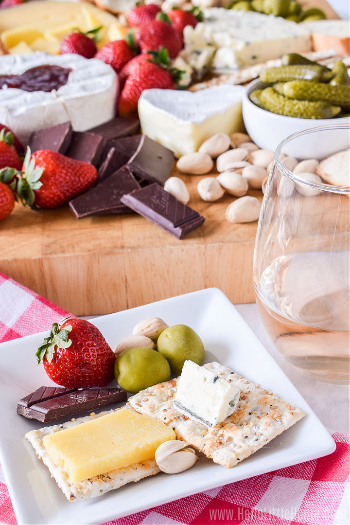 A plate of cheese and crackers next to a glass of wine with more food in the background.