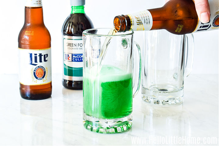 A hand pouring beer into a glass mug.