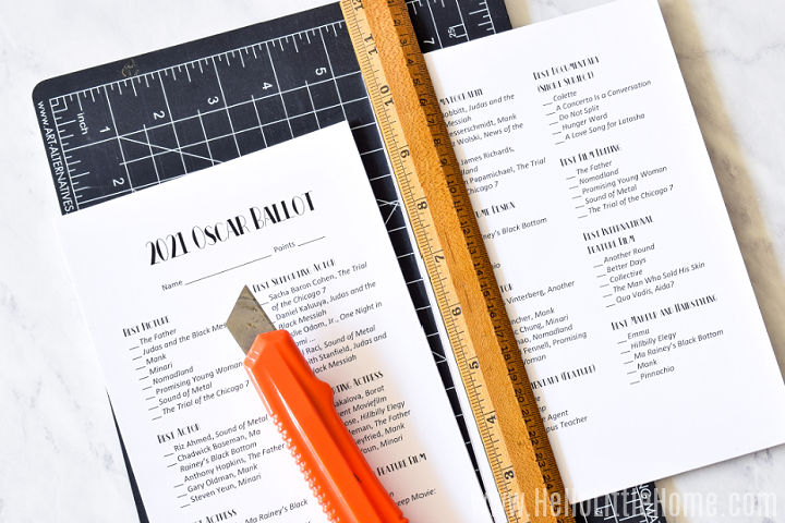 A cutting mat, utility knife, ruler, and sheets of paper arranged on a marble counter.