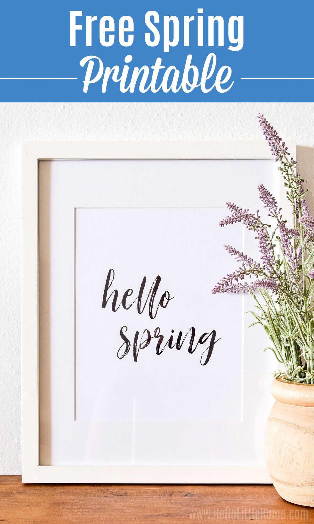 The Hello Spring print in a white frame and a lavender plant on a wood table.
