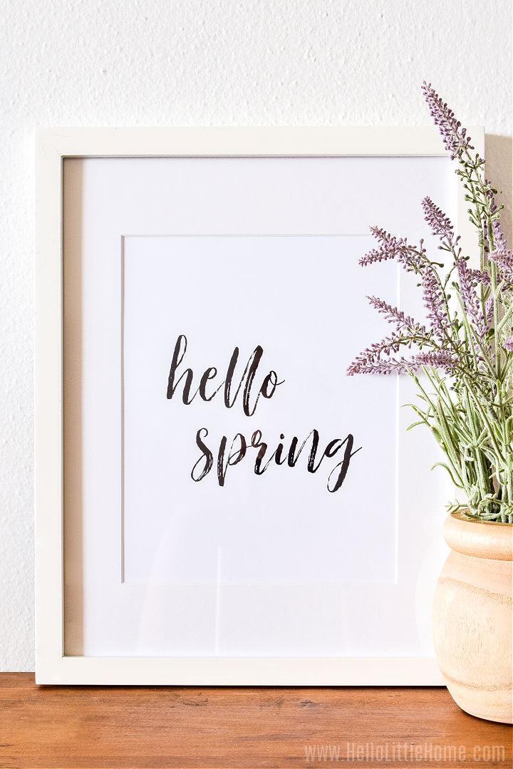 A framed brush script print next to a lavender plant on a wood table.