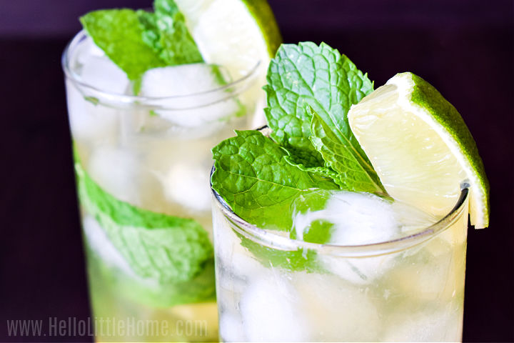Closeup of the finished cocktail garnished with lime wedges and mint sprigs.