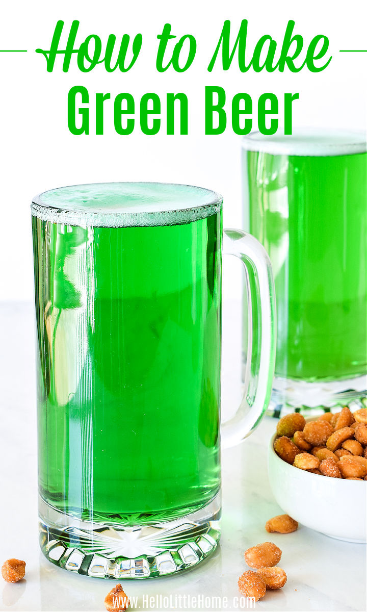 A mug of Green Beer on a counter next to a bowl of peanuts.