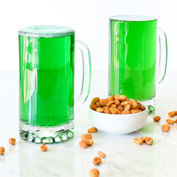 Two Green Beers served in mugs next to a bowl of peanuts.