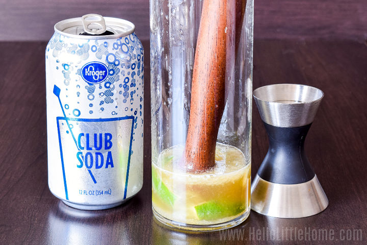A club soda can, glass with muddled lime wedges, and jigger on a wood table.
