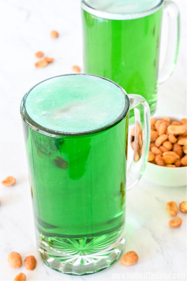 Two of the finished drinks on a marble counter with a bowl of peanuts.