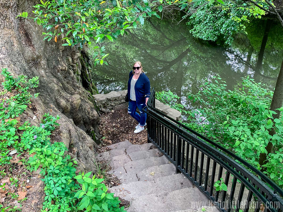 A woman standing at the bottom of a staircase next to a giant tree with the creek behind her.