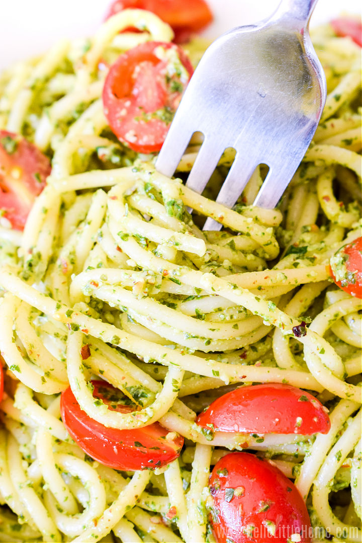 Closeup of a fork twirling pesto pasta.