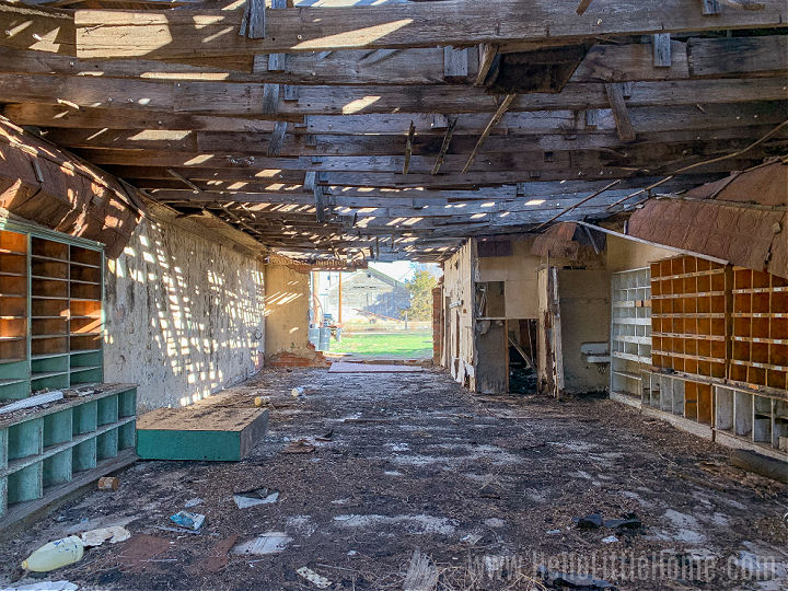The inside of a crumbling building with shelf-lined walls.