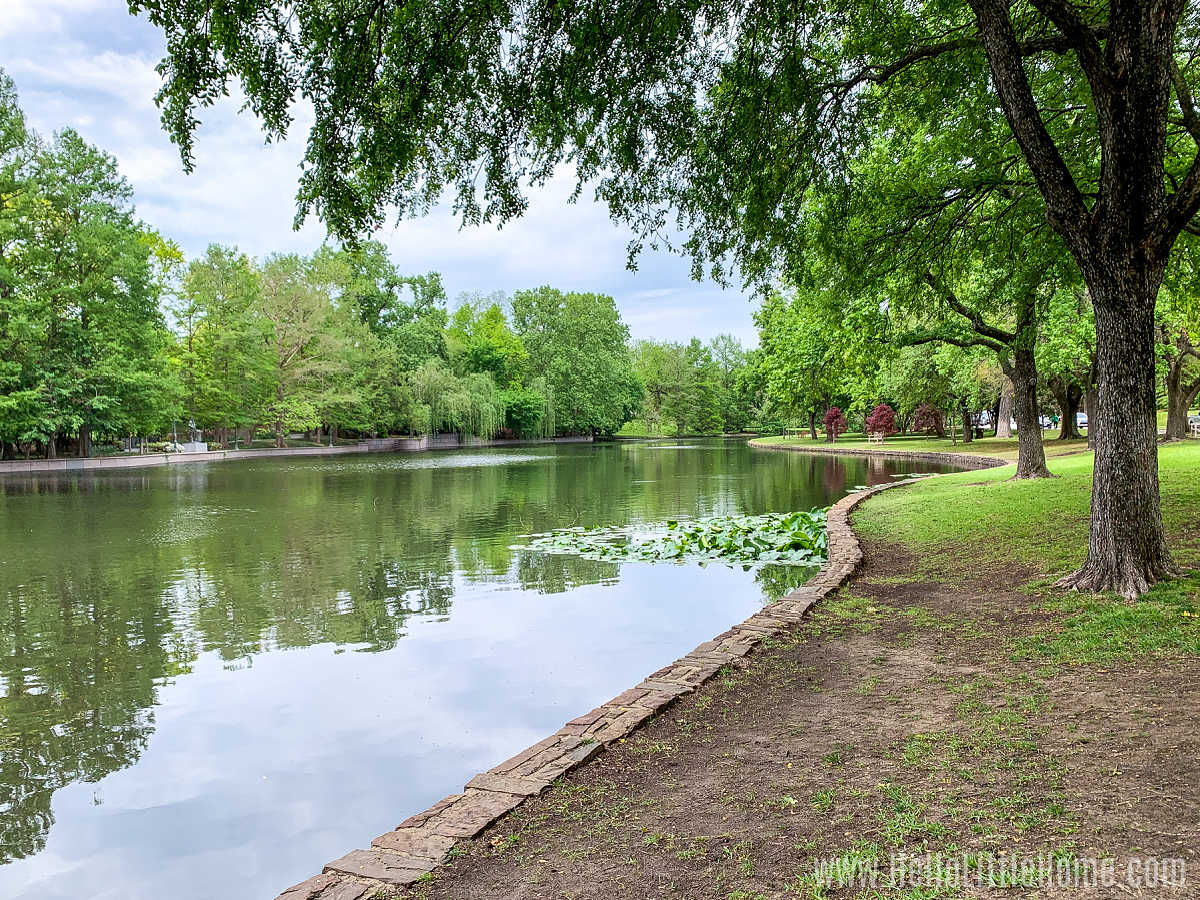 Trees lining the edges and reflecting the water of Exall Lake (Turtle Creek) in the park.