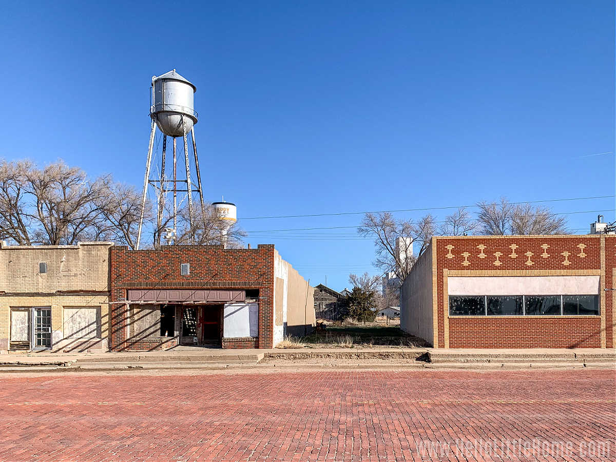 Vacant stores lining Main Street with a water tower in the background.