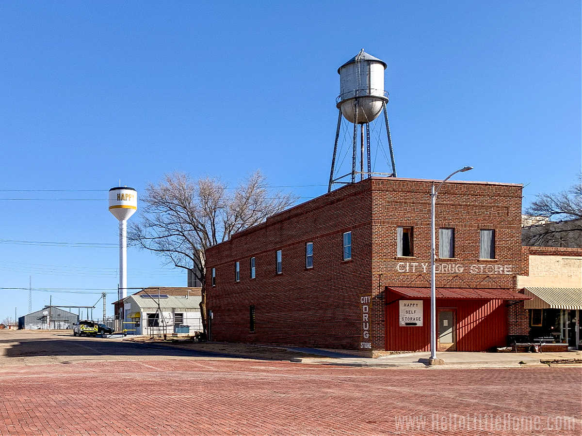 A street corner with a brick building with two water towers behind it.