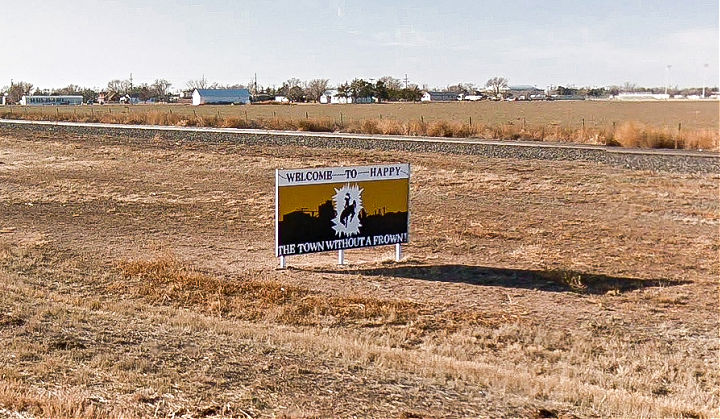 The Happy, Texas welcome sign in a roadside field.