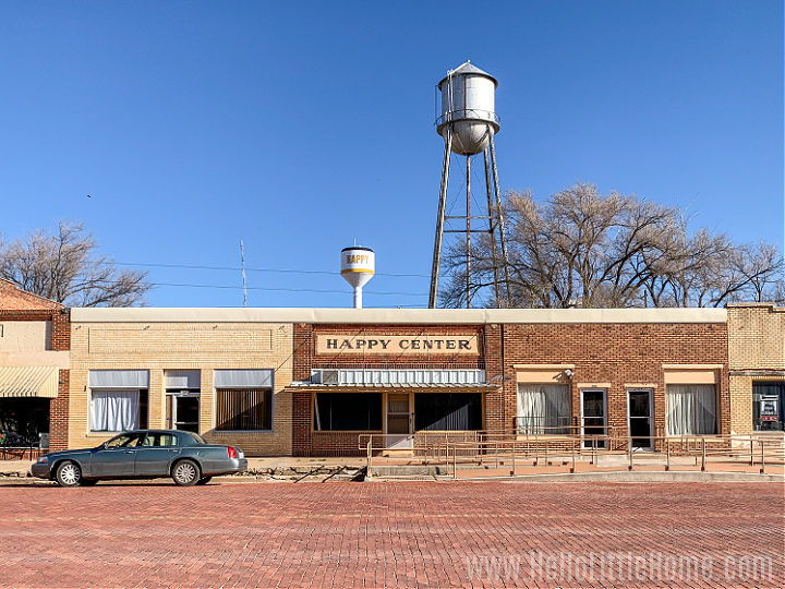 An empty brick street lined with store fronts in Happy, Texas.