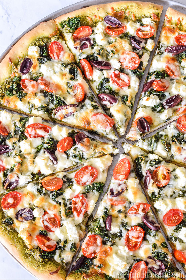 Half a pizza topped with kale, tomatoes, olives, and feta on a pizza pan.