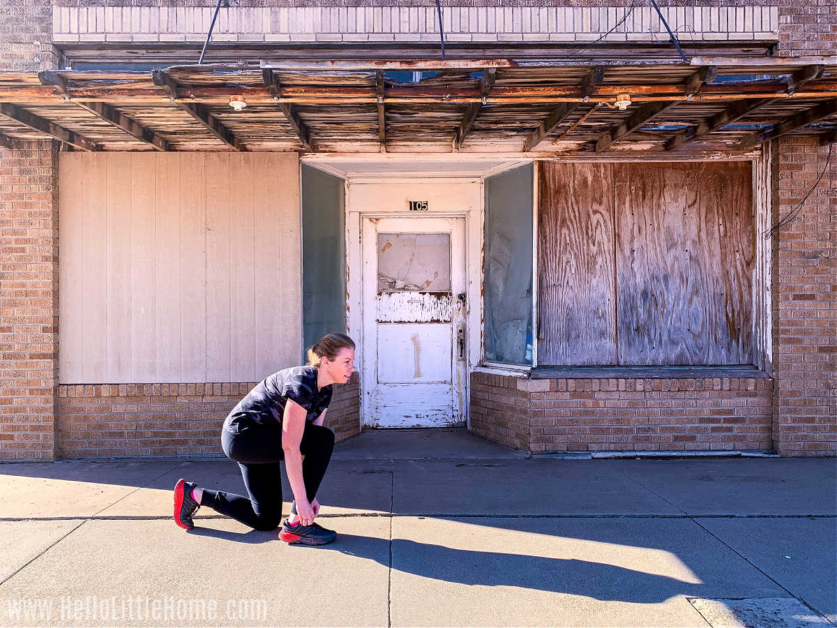 A woman tying her shoe in front of a vacant store.