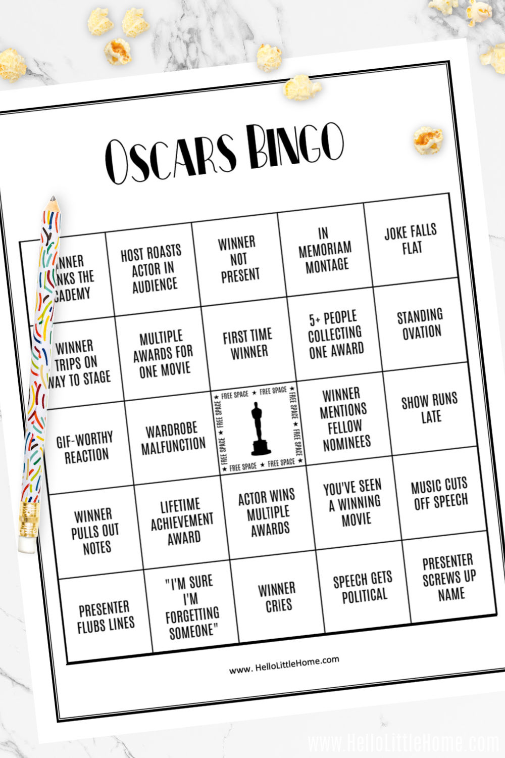 A closeup of the Oscar Party Bingo Card topped with a pencil and a few popcorn kernels.